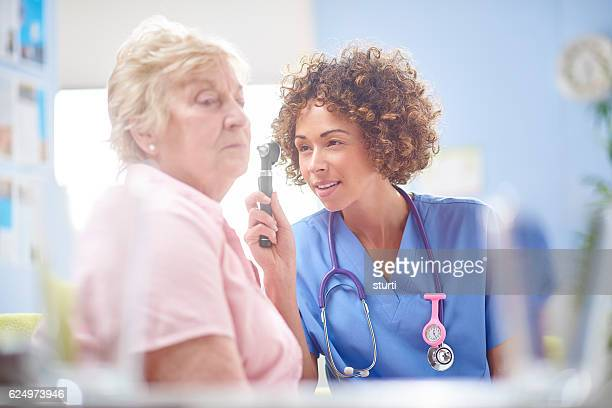 female doctor using otoscope