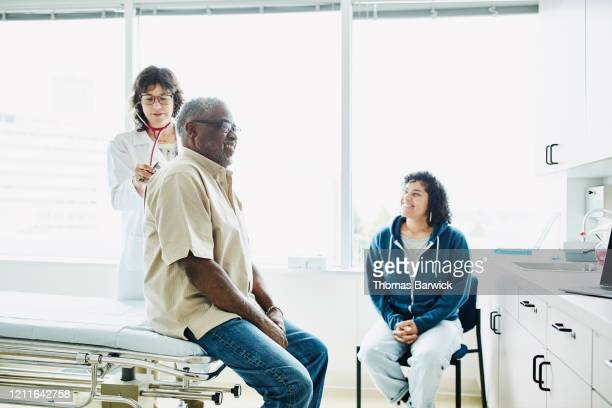 female doctor using stethoscope to listen to senior male patients breathing during exam - leanincollection stock pictures, royalty-free photos & images