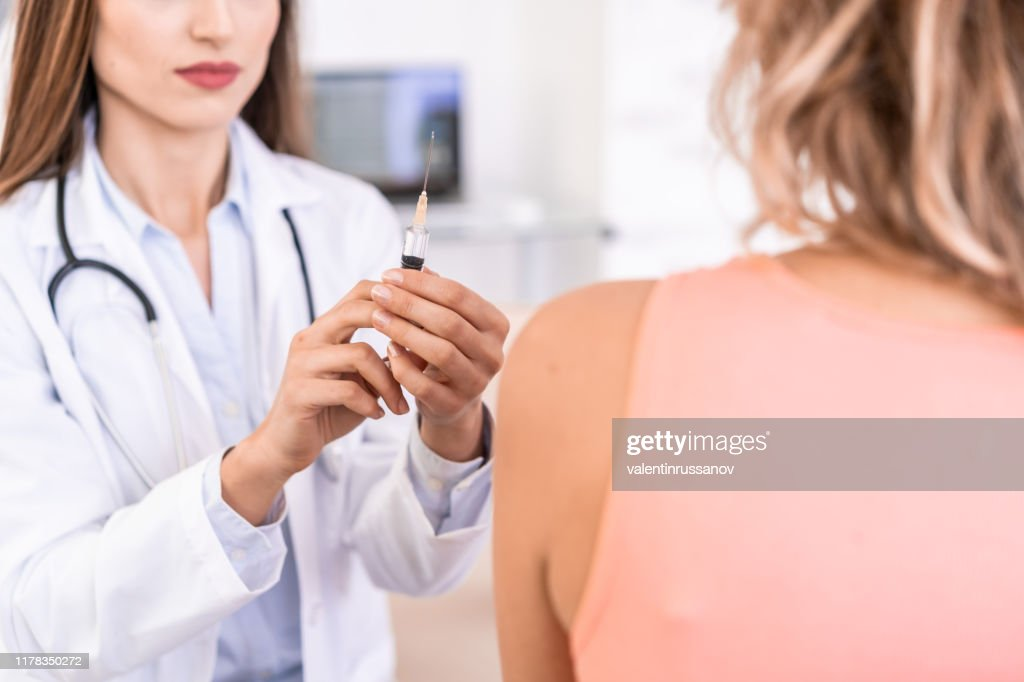 Vrouwelijke arts die een patiënt vaccineert : Stockfoto