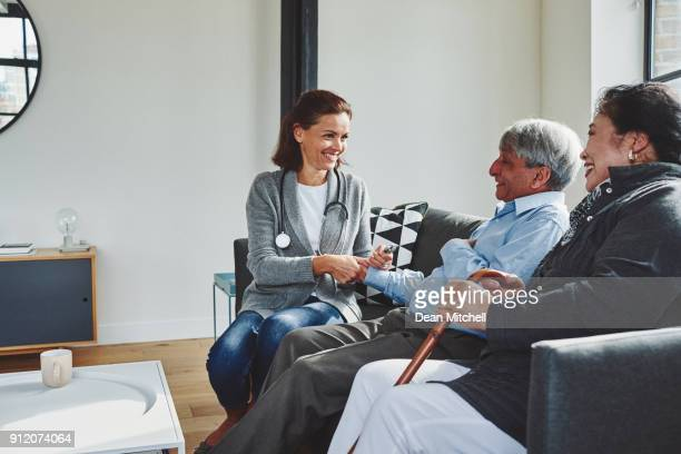 female doctor visiting elderly couple - visit stock pictures, royalty-free photos & images