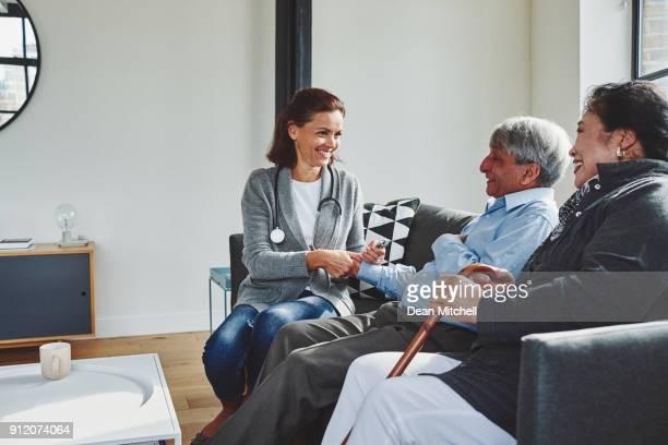 Female doctor visiting elderly couple