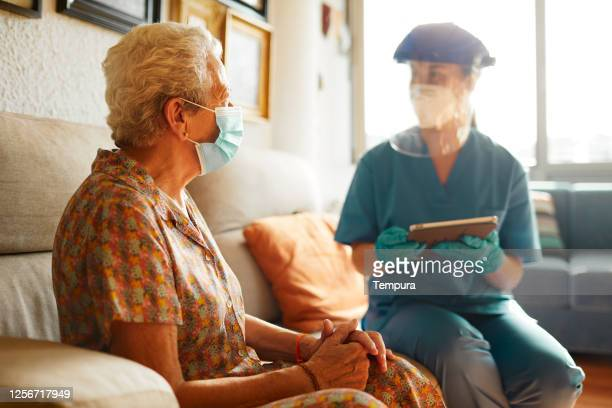 a female doctor visits a senior woman at the nursing home. - healthcare worker stock pictures, royalty-free photos & images