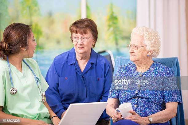 Female doctor visits elderly woman patient in nursing home. Laptop.