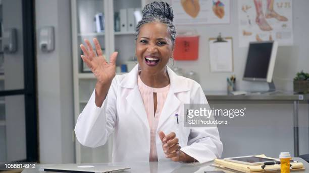female doctor waves at camera during web conference - waving stock pictures, royalty-free photos & images