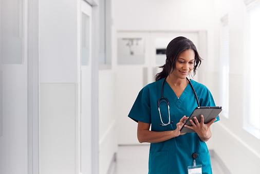 Female Doctor Wearing Scrubs In Hospital Corridor Using Digital Tablet 1205548238