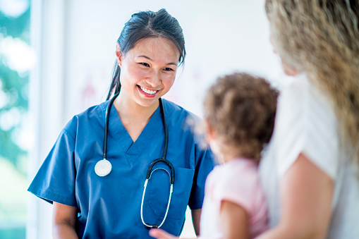 Female doctor with a young girl patient and her mother 1064730866