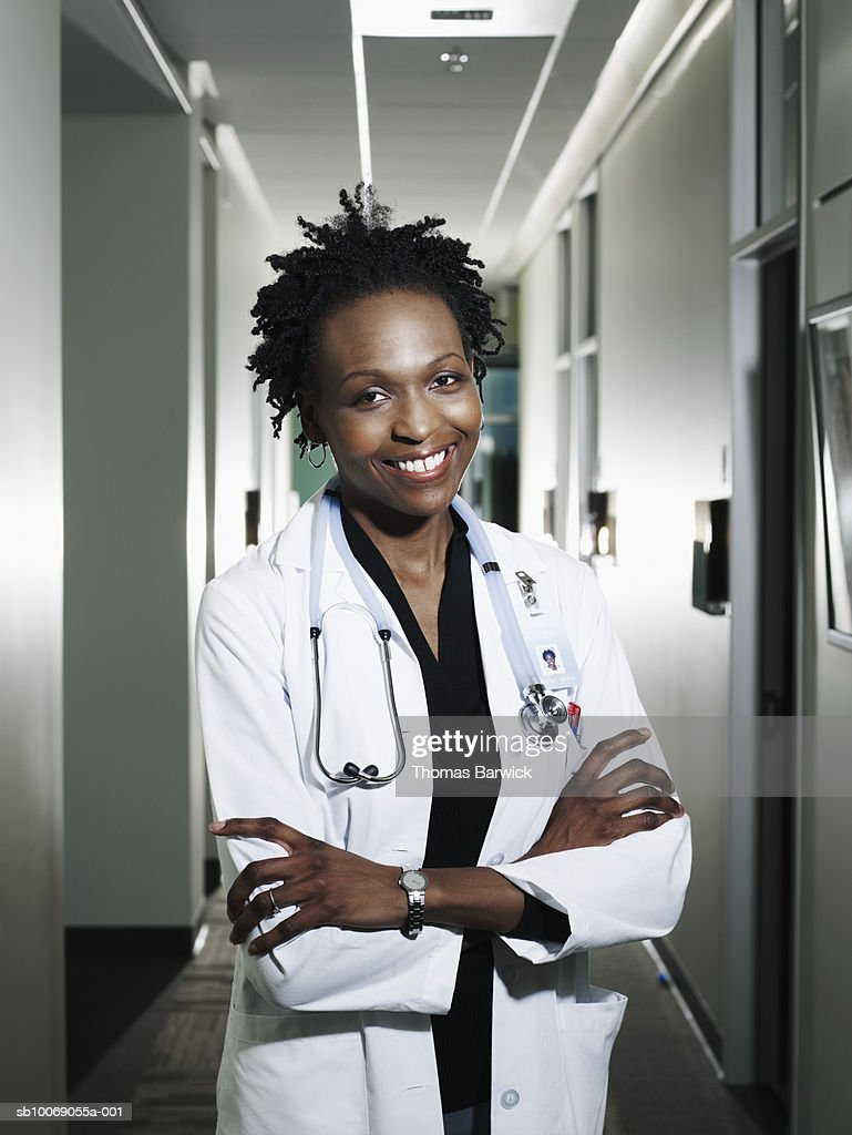Female doctor with arms crossed smiling, portrait : Stockfoto