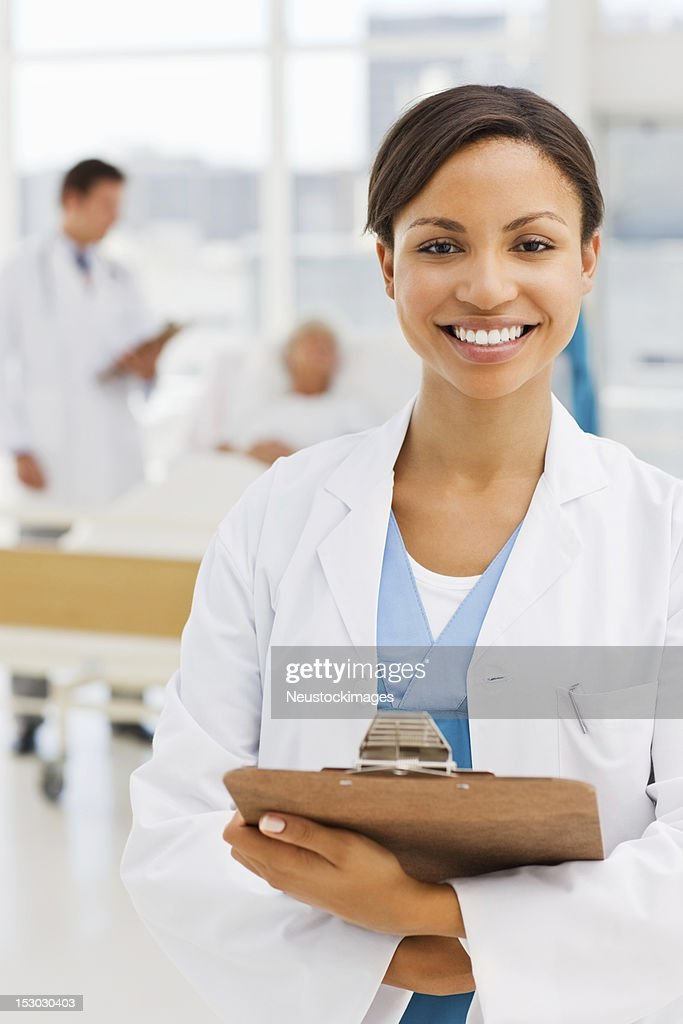 Female doctor with colleague and patient in background : Stock Photo