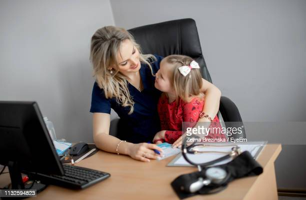 Female Doctor With Cute Girl Sitting On Chair At Hospital
