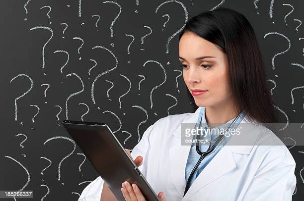 Female doctor with digital tablet in front of question marks