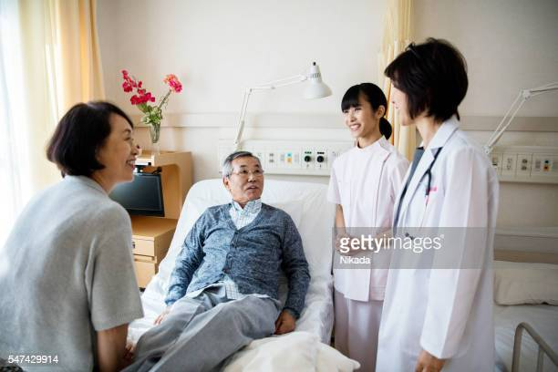 female Doctor with nurse talking to senior couple in hospital