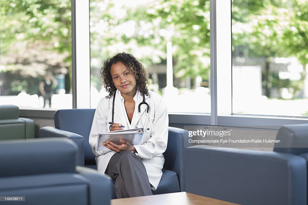 Female doctor with stethoscope, smiling : Stock Photo