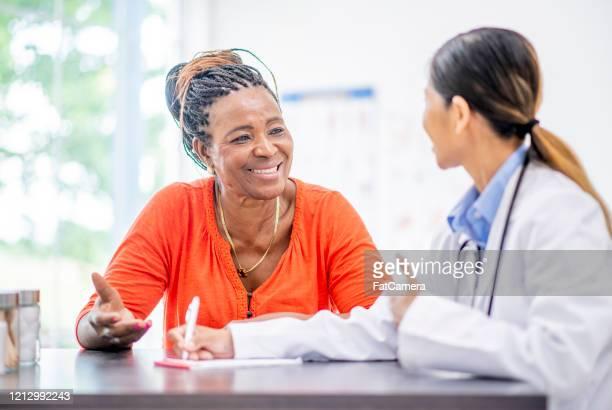 処方箋のストック写真を書く女性医師 - オレンジ色のシャツ ストックフォトと画像