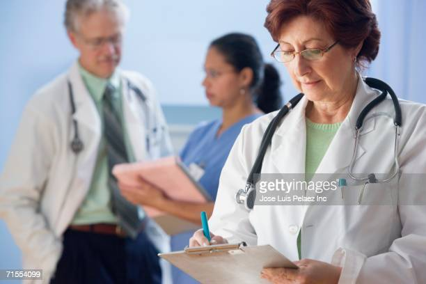 Female doctor writing in chart