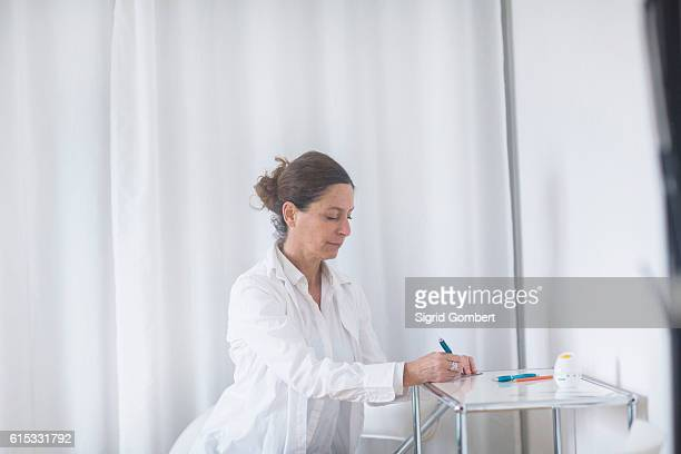 female doctor writing prescription in hospital, freiburg im breisgau, baden-württemberg, germany - sigrid gombert stock pictures, royalty-free photos & images