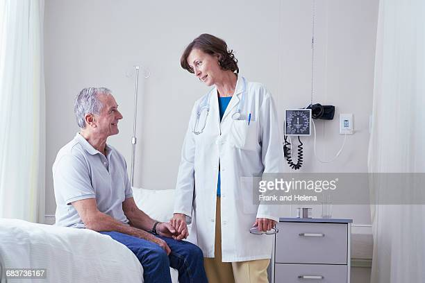 Female doctors explaining to senior male patient on hospital bed