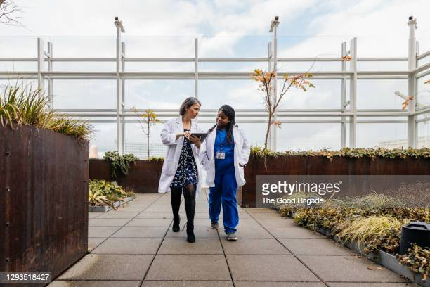 female doctors talking while walking on rooftop of hospital - healthcare stock pictures, royalty-free photos & images