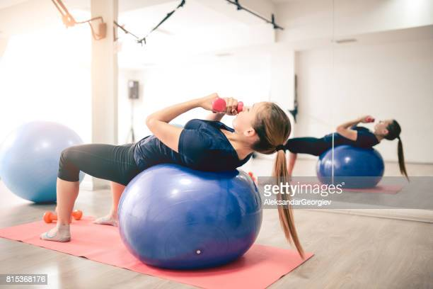 Female Doing Abs with Weights on Exercise Ball in Gym
