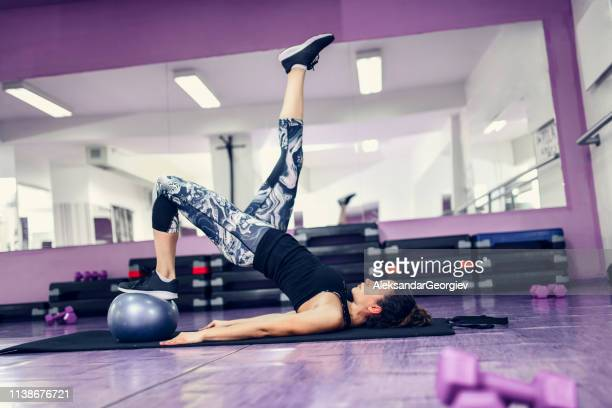 female doing pilates exercise in gym with fitness ball - aleksandar georgiev stock photos and pictures