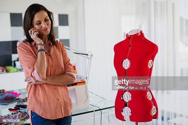 Female dress designer talking on a mobile phone in her office