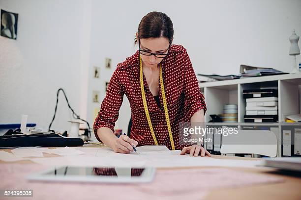 Female dressmaker drawing in studio.