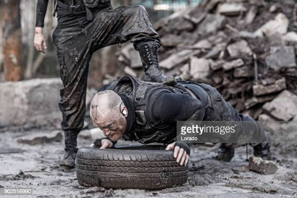 Female drill instructor training shaved male soldier doing push ups outdoors in the mud