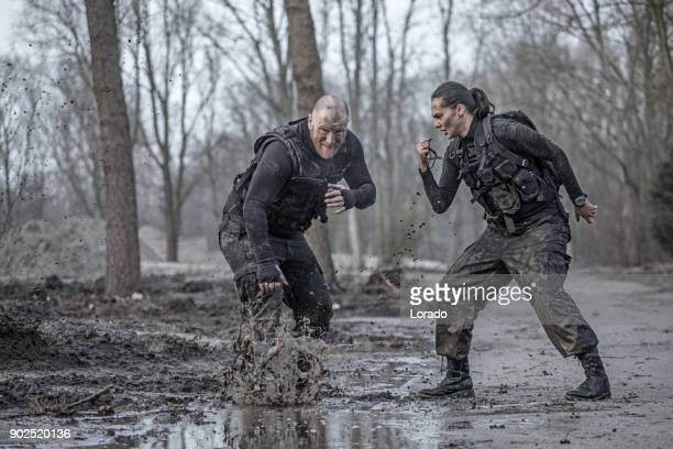 Female drill instructor training shaved male soldier doing sprints outdoors in the mud