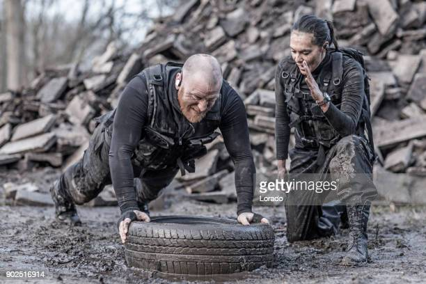 Female drill instructor training shaved male soldier in push ups outdoors in the mud