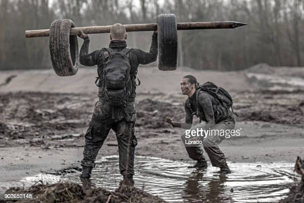 Female drill instructor training shaved male soldier outdoors in the mud