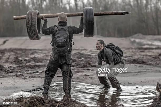 Weiblichen Drill Instructor Training rasiert männlichen Soldaten im Freien im Schlamm