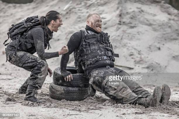 Female drill instructor training shaved male soldier with tires outdoors in the mud