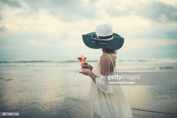 female drinking cocktail and enjoying the sunset ocean view - sundress stock pictures, royalty-free photos & images