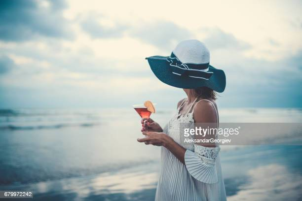 Female Drinking Cocktail and Enjoying the Sunset Ocean View