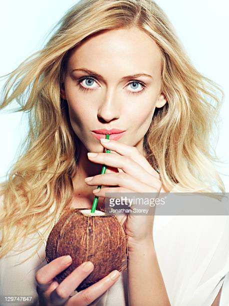 Female drinking from a straw in a coconut