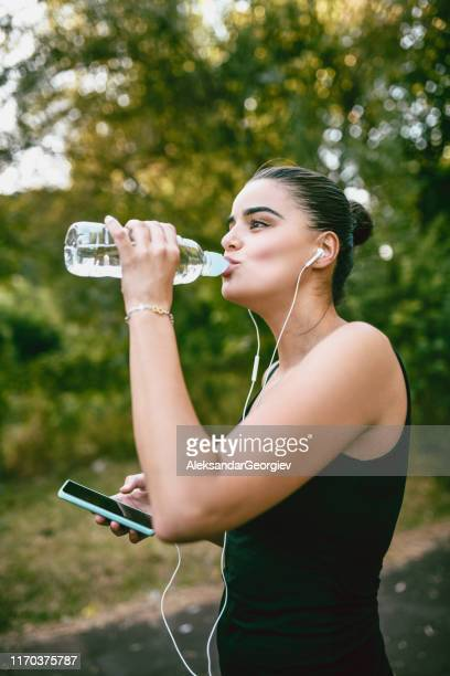 female drinking water and listening to music after training - colors soundtrack stock pictures, royalty-free photos & images