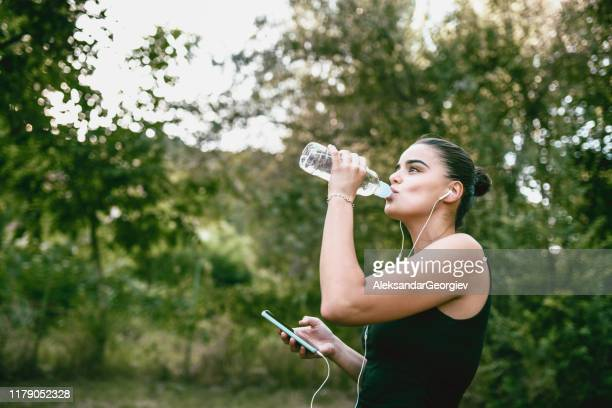 female drinking water and setting up playlist before training - colors soundtrack stock pictures, royalty-free photos & images