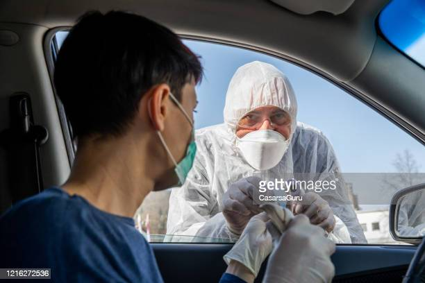 female driver at quarantine road control for covid-19 testing showing her id document - n95 face mask stock pictures, royalty-free photos & images