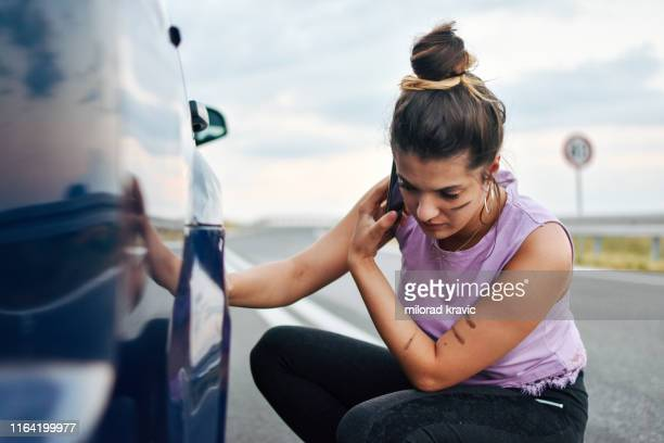 female driver broken down on country road - flat tire stock pictures, royalty-free photos & images