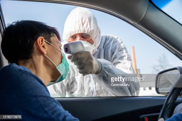 female driver exposing her forehead for the covid-19 body temperature testing - infrared thermometer stock pictures, royalty-free photos & images