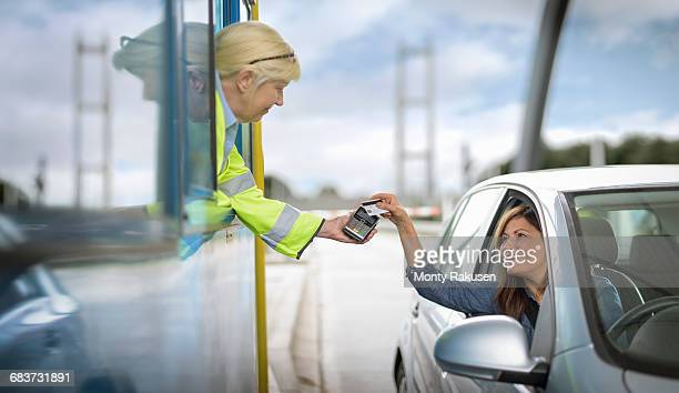 Female driver in car paying toll booth at bridge