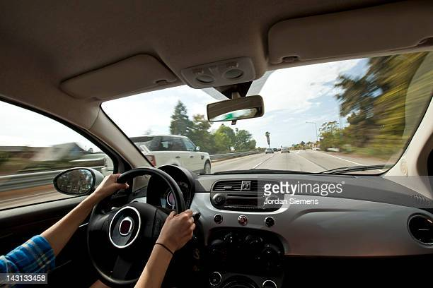A female driving on a highway.
