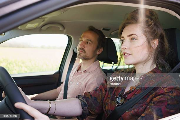 Female driving while sitting besides man in car