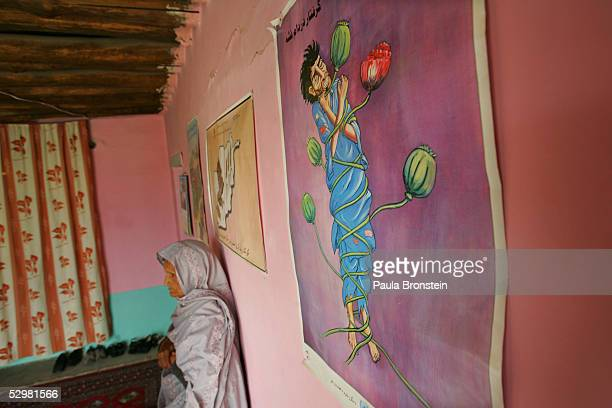 A female drug addict stands next to a antidrug poster at the Nejat Center women's community based drug rehabilitation program May 23 2005 in Kabul...