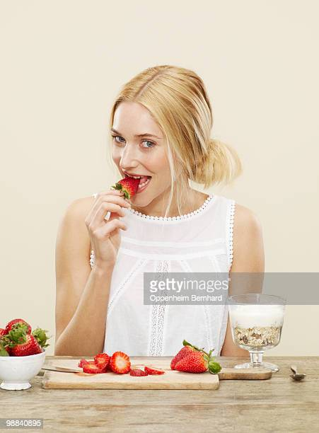 female eating a fresh strawberry