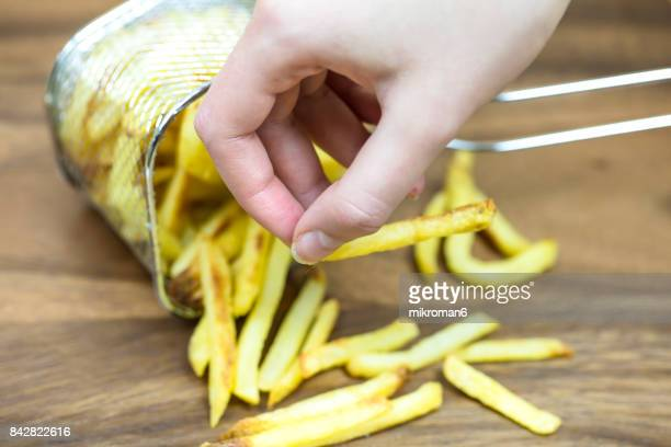 Female eating chips. A small wire basket of fried potatoes, chips on a wooden table.