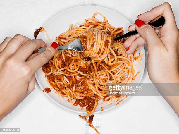 female eating spaghetti, overhead view - pasta stock pictures, royalty-free photos & images