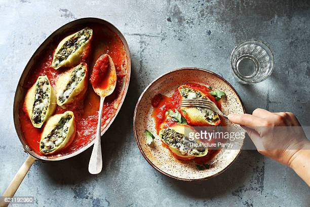 female eating stuffed pasta shells with ricotta cheese and spinach - stuffed stock pictures, royalty-free photos & images