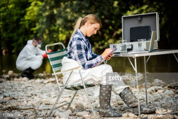 a female ecologist analyzes the state of water in a forest river - ecologist stock pictures, royalty-free photos & images