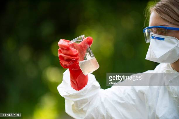 female ecologist examines the dirty water in the flask - ecologist stock pictures, royalty-free photos & images
