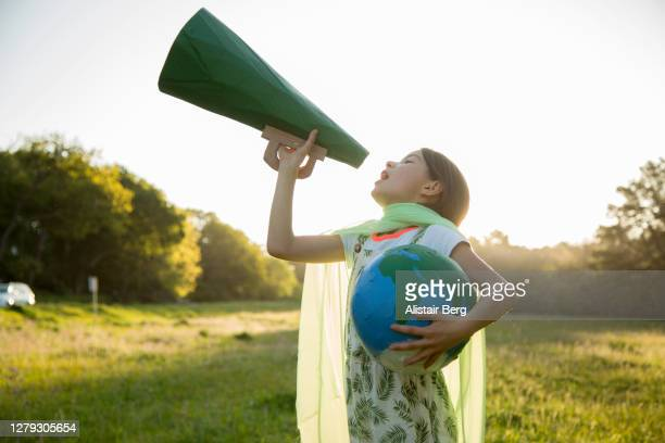 female eco-warrior shouting into a megaphone - climate stock pictures, royalty-free photos & images